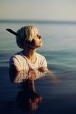 Schönes Mädchen im weißen Hemd, das im Wasser bei Sonnenuntergang aufwirft Stockbild