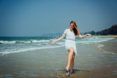 Sch?nes M?dchen im wei?en Kleid genie?en und entspannen sich auf dem Strand Reise und Ferien lizenzfreie stockfotos