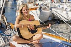 Schönes Mädchen-junge Frau, die Gitarre auf einem Boot spielt Stockfoto
