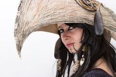 Schönes Mädchen kleidete in Hexen- oder Medizinmannhalloween-Kostüm mit schwarzen Federn und im Krähenkopf auf dem weißen Hinterg Lizenzfreies Stockfoto