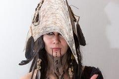 Schönes Mädchen kleidete in Hexen- oder Medizinmannhalloween-Kostüm mit schwarzen Federn und im Krähenkopf auf dem weißen Hinterg Lizenzfreies Stockbild