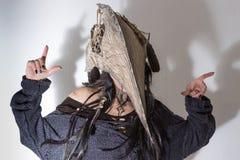 Schönes Mädchen kleidete in Hexen- oder Medizinmannhalloween-Kostüm mit schwarzen Federn und im Krähenkopf auf dem weißen Hinterg Stockfotografie