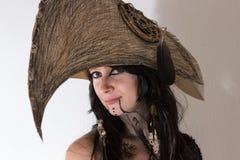 Schönes Mädchen kleidete in Hexen- oder Medizinmannhalloween-Kostüm mit schwarzen Federn und im Krähenkopf auf dem weißen Hinterg Stockfotos
