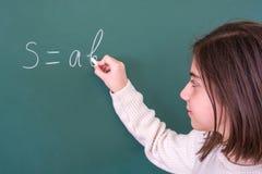 Schönes Mädchen löst mathematische Aufgabe an Bord stockfoto