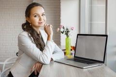 Schönes Mädchen lehnt ihre Ellbögen auf Tabelle mit Laptop lizenzfreie stockbilder
