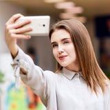Schönes Mädchen macht selfie im Einkaufszentrum stockbild
