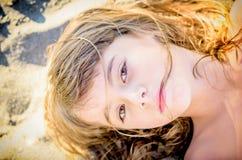 Schönes Mädchen mit acht Jährigen, das auf den Strand legt Lizenzfreie Stockfotografie