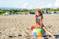 Schönes Mädchen mit acht Jährigen, das mit dem Ball auf dem Strand spielt Lizenzfreie Stockfotos