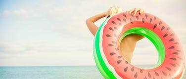 Schönes Mädchen mit aufblasbarem Ring steht auf dem Strand und betrachtet das Meersommerferien Fahnenkonzept stockbild
