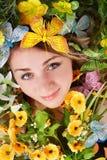 Schönes Mädchen mit Basisrecheneinheit und Blume auf Gras. Stockfotos