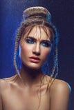 Schönes Mädchen mit blauem Make-up im Wasser fällt Stockbild
