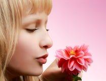 Schönes Mädchen mit Blume auf rosafarbenem Hintergrund Lizenzfreie Stockfotografie