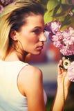 Schönes Mädchen mit Blumen, Frühlings-Magie Kirschblüte-Rosablumen Mit weißem Pelz des Zaubers und Sonnenbrille mit Weinlesetasch Stockbilder