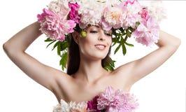Schönes Mädchen mit Blumenpfingstrosen Porträt einer jungen Frau mit Blumen in ihrem Haar und in einem Kleid von Blumen Lizenzfreie Stockfotos