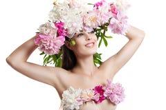 Schönes Mädchen mit Blumenpfingstrosen Porträt einer jungen Frau mit Blumen in ihrem Haar und in einem Kleid von Blumen Stockfoto
