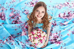 Schönes Mädchen mit Blumenstrauß von den Blumen, die auf dem Boden sitzen Lizenzfreies Stockfoto