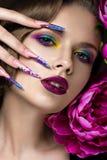 Schönes Mädchen mit buntem Make-up, Blumen, Retro- Frisur und langen Nägeln Maniküredesign Die Schönheit des Gesichtes lizenzfreie stockfotos