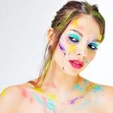 Schönes Mädchen mit bunter Farbe spritzt auf Gesicht Stockfotografie