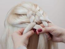 Schönes Mädchen mit dem blonden Haar, Friseur spinnt eine Zopfnahaufnahme, in einem Schönheitssalon lizenzfreies stockbild