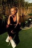 Schönes Mädchen mit dem blonden Haar im Badeanzug, der an Sonnenuntergang beac aufwirft Stockbilder