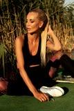 Schönes Mädchen mit dem blonden Haar im Badeanzug, der an Sonnenuntergang beac aufwirft Stockbild