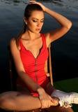 Schönes Mädchen mit dem blonden Haar im Badeanzug, der an Sonnenuntergang beac aufwirft Lizenzfreie Stockbilder