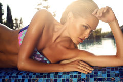 Schönes Mädchen mit dem blonden Haar im Bikini, der neben einem Swimmingpool aufwirft Lizenzfreie Stockfotografie