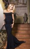 Schönes Mädchen mit dem blonden Haar im schwarzen Kleid Stockfotografie