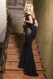Schönes Mädchen mit dem blonden Haar im schwarzen Kleid Stockbilder