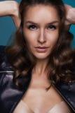 Schönes Mädchen mit dem dunklen gelockten Haar und blauen den Augen, die Ohren bedecken Lizenzfreies Stockfoto