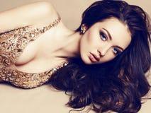 Schönes Mädchen mit dem dunklen Haar im luxuriösen Pailletten-Kleid Stockbilder
