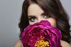Schönes Mädchen mit dem dunklen Haar und großer Blume nahe Gesicht Große PU Lizenzfreie Stockfotografie