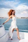 Schönes Mädchen mit dem flatternden weißen Kleid und rotem gelocktem Haar, die an Bord des Schiffs aufwerfen stockfoto
