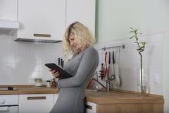 Schönes Mädchen mit dem gelockten Haar passt absorbedly etwas in der Tablette auf Lizenzfreie Stockfotografie