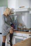 Schönes Mädchen mit dem gelockten Haar setzt auf dem Küchentisch und macht Kaffee Stockfotos