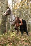 Schönes Mädchen mit dem hübschen Kleid, das nahe bei nettem Pferd steht Stockbilder