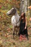 Schönes Mädchen mit dem hübschen Kleid, das nahe bei nettem Pferd steht Lizenzfreie Stockfotos