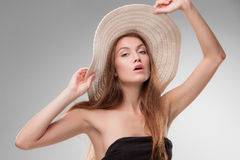 Schönes Mädchen mit dem Hut, der im Studio aufwirft Lizenzfreies Stockfoto