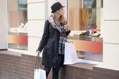 Schönes Mädchen mit dem Käufer, der windoew Shop betrachtet Lizenzfreie Stockfotografie