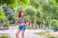 Schönes Mädchen mit dem Lächeln und dem Halten des Zeigefingers Ein Mädchen in einem karierten Hemd und kurzen in Denimkurzen hos stockfoto