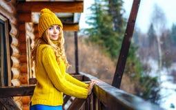 Schönes Mädchen mit dem langen blonden gelockten Haar in einem Strickpulli und in einem Hut Stockfoto