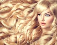 Schönes Mädchen mit dem langen gelockten blonden Haar Stockfotos