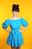 Schönes Mädchen mit dem langen gewellten Haar, das im blauen Kleiderlächeln trägt Stockfoto