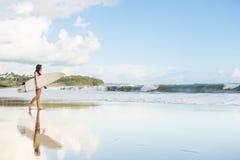 Schönes Mädchen mit dem langen Haar auf dem Strand mit Surfbrett stockbilder