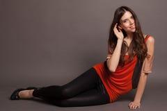 Schönes Mädchen mit dem langen Haar, das auf dem Boden sitzt Lizenzfreie Stockbilder