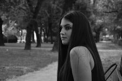 Schönes Mädchen mit dem langen Haar in der Liebe, die im Park sitzt Stockbild
