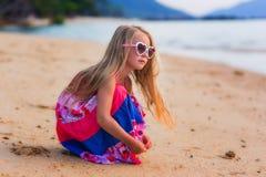 Schönes Mädchen mit dem langen Haar in der Sonnenbrille, die im Sand auf dem Strand spielt und den Abstand untersucht Stockbild