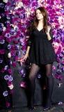 Schönes Mädchen nahe der Wand mit violetten Blumen Stockfotos