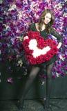 Schönes Mädchen nahe der Wand mit violetten Blumen Stockfoto