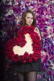 Schönes Mädchen nahe der Wand mit violetten Blumen Lizenzfreies Stockfoto